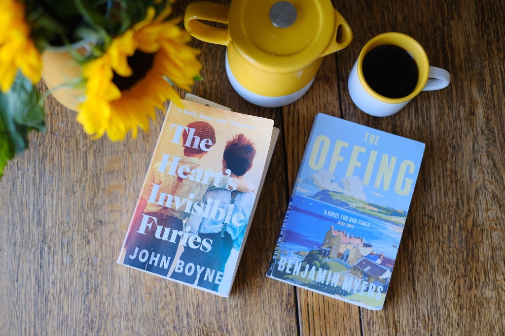 Two books on a coffee table with coffee cup and sunflowers in the background. The books are The Heart's Invisible Furies by John Boyne and The Offing by Benjamin Myers.