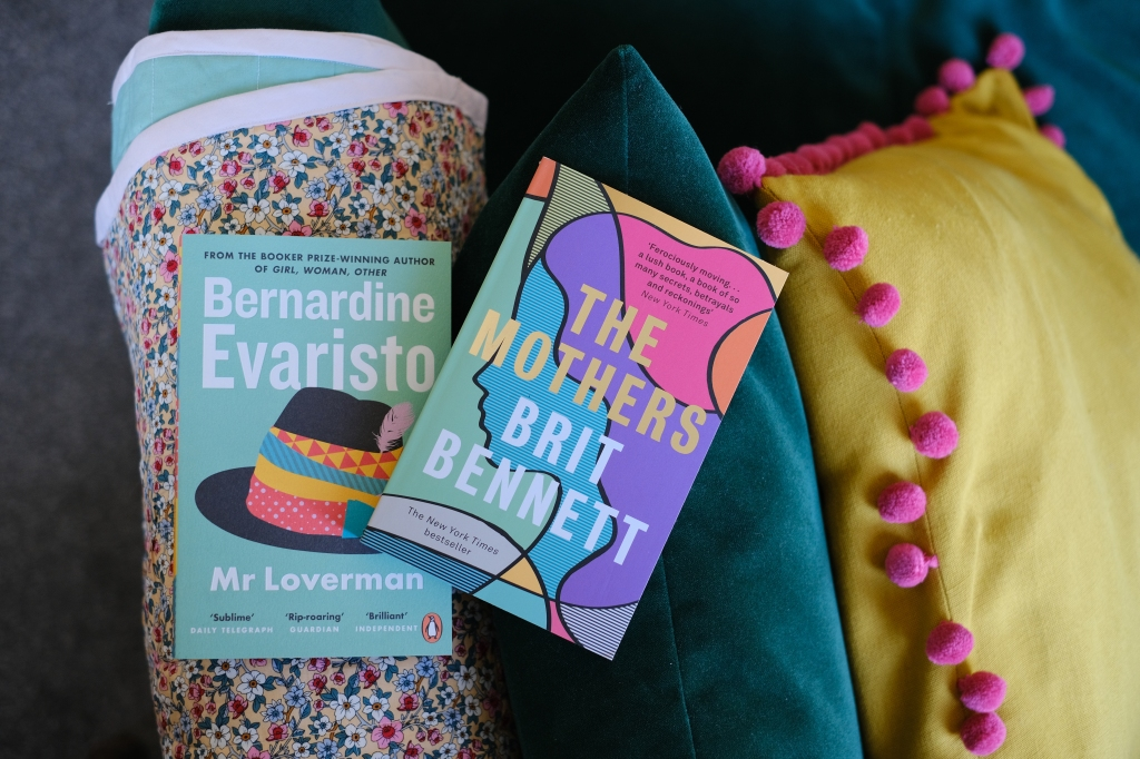 Two books on a green sofa. The books are Mr Loverman by Bernadine Evaristo and The Mothers by Brit Bennett.