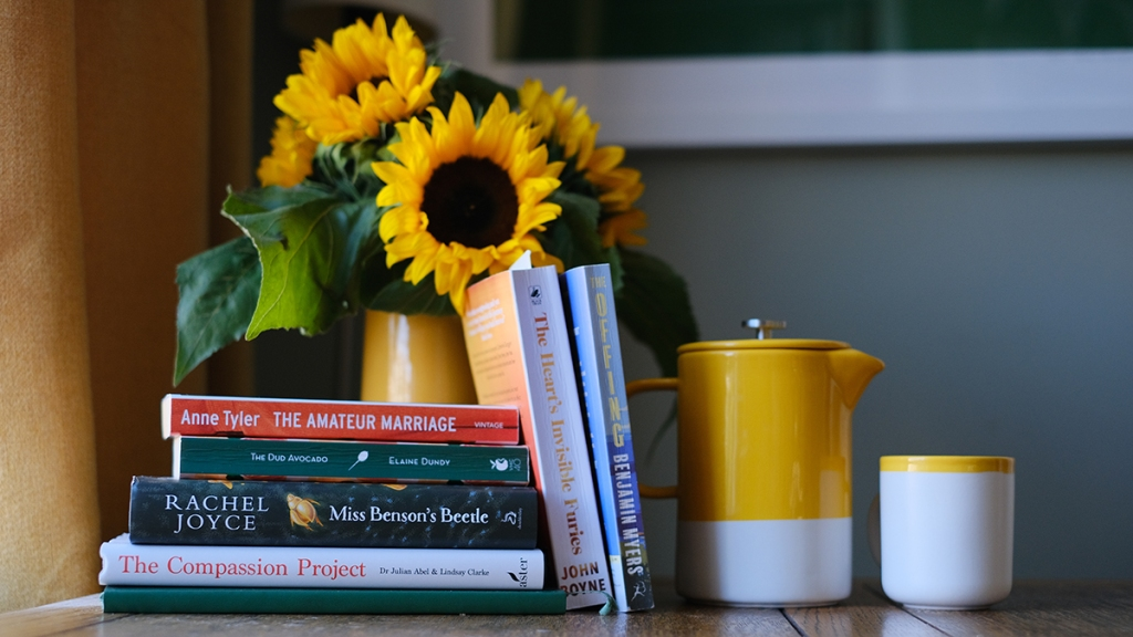 A table featuring a jug of sunflowers and a stack of books: The Amateur Marriage, The Dud Avocado, Miss Benson's Beetle, The Compassion Project, The Heart's Invisible Furies and The Offing