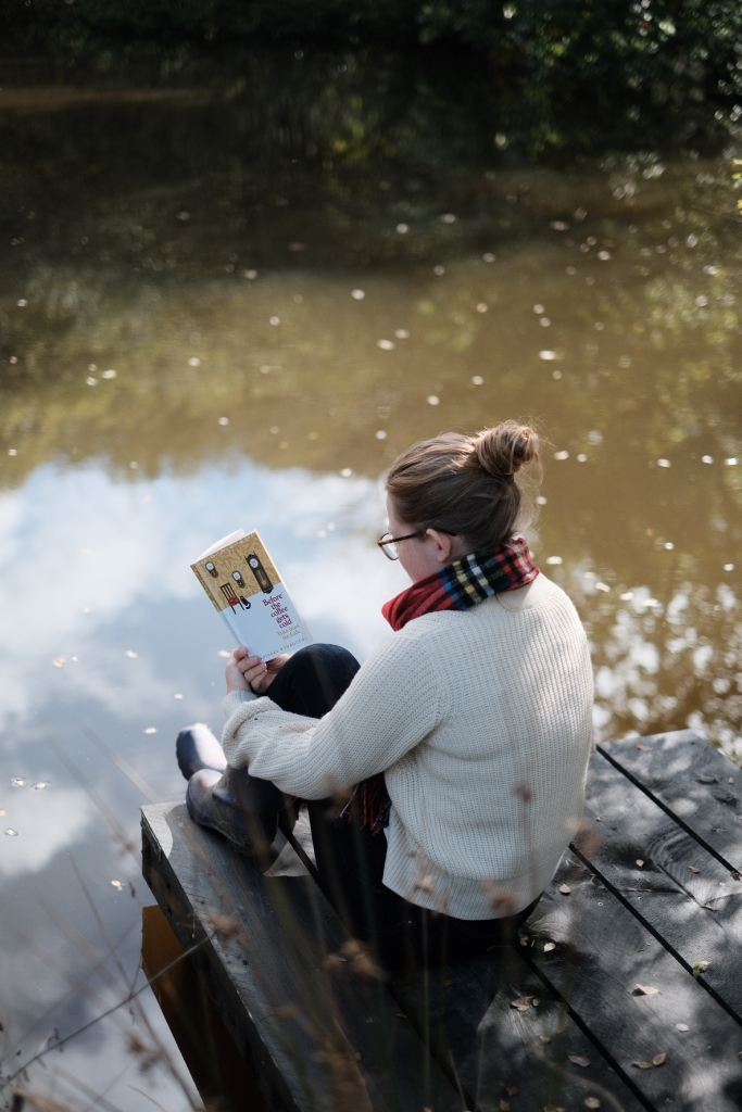 Libby sits on a deck by a lake reading Before the Coffee Gets Cold, wearing a jumper and scarf.