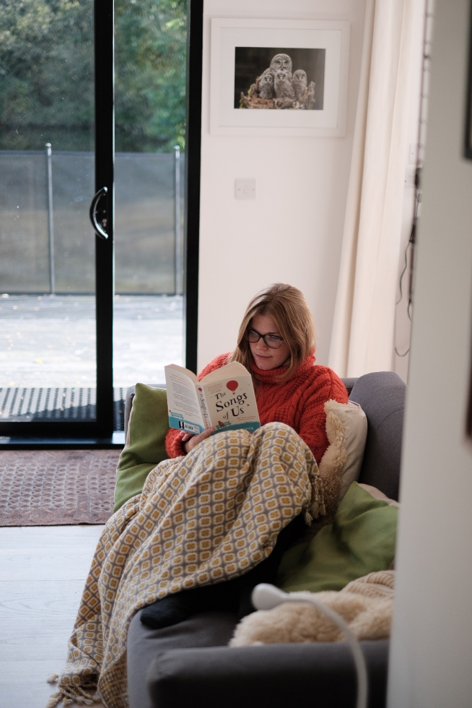 Libby sat on a sofa under a blanket and wearing an orange jumper, reading The Songs of Us.