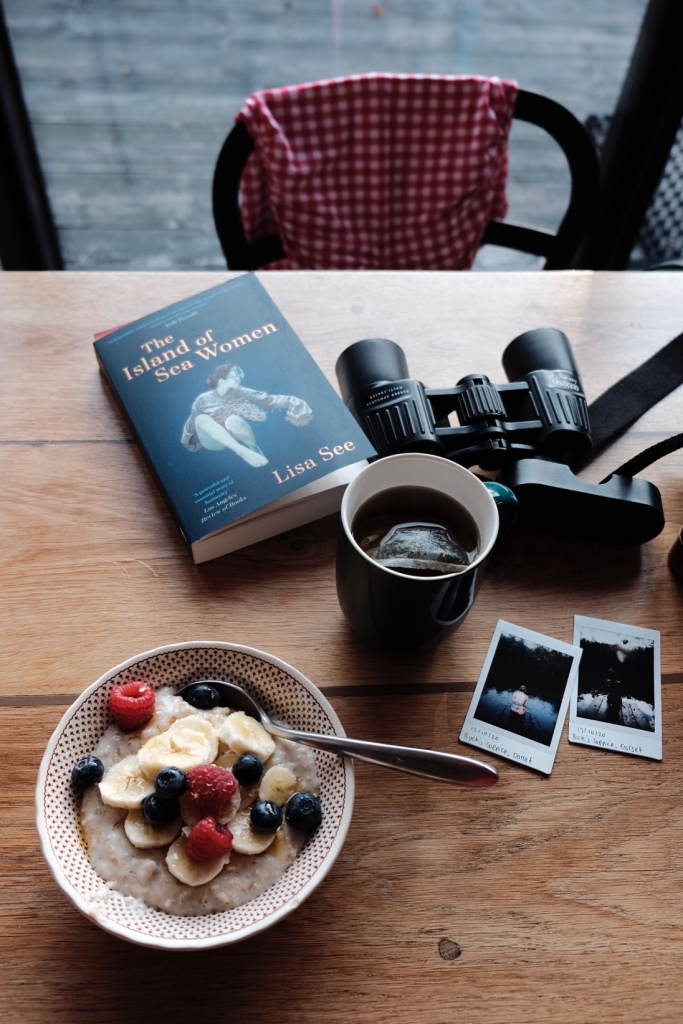 A kitchen table featuring a bowl of porridge, a cup of tea, a pair of binoculars and a book, titled The Island of Sea Women.