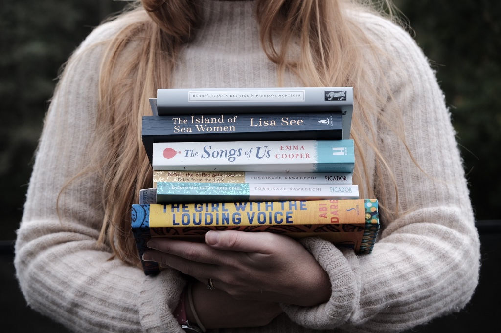 A photo of Libby holding a stack of books: Daddy Goes A-Hunting, The Island of Sea Women, The Songs of Us, Before the Coffee Gets Cold and The Girl with the Louding Voice